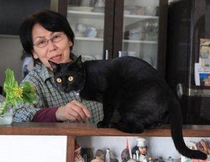 黒猫「あぽろ」。後ろにいるのが吉田幸子さん