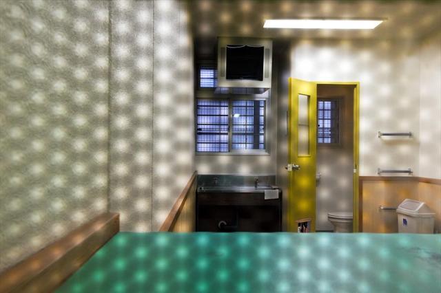 東日本入国管理センターの和室。穴が水玉状に開いた通話用の仕切り越しに、廊下から室内を撮影した=茨城県牛久市、鬼室黎撮影
