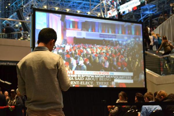 トランプ氏優勢を伝える選挙特番を見つめる人々