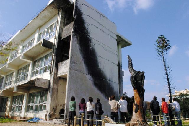 米軍ヘリが墜落した校舎を眺めるゼミの学生たち=2005年4月4日、沖縄県宜野湾市の沖縄国際大学で