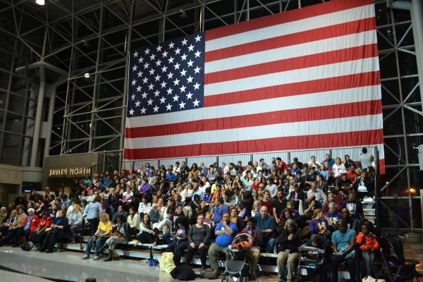 ヒラリー氏の集会会場に飾られていた巨大なアメリカ国旗。その前に、いろんな人種の人々が座っていた
