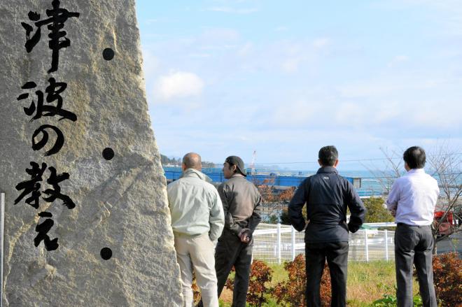 福島沖地震が起きた11月22日午前9時過ぎ、東日本大震災の碑の前で、心配そうに海を見つめる避難者=気仙沼市本吉町