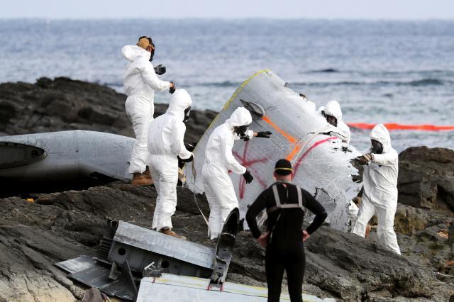 エンジンカッターを使い切断したオスプレイの一部を運ぶ米軍関係者ら=2016年12月16日、沖縄県名護市、関田航撮影
