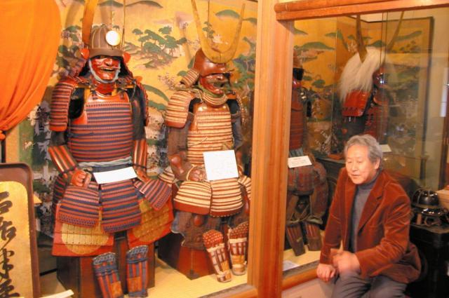 井伊家の甲冑の数々。説明するのは井伊達夫館長=2006年2月4日、京都市東山区花見小路四条下ルの「京都井伊美術館」で