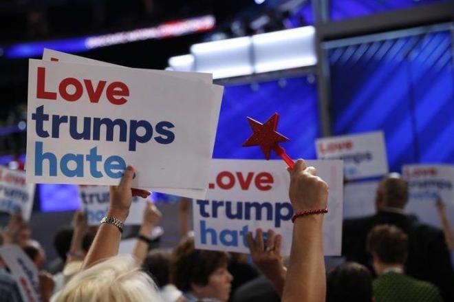 「Love trumps hate.」のプラカードをかかげる人々=ロイター