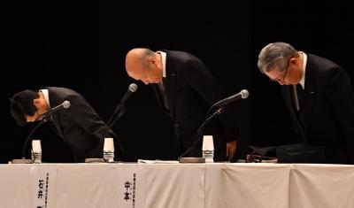 記者会見で謝罪する電通の石井直社長(中央)ら=2016年12月26日