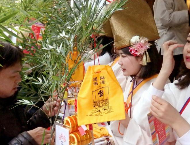 2017年1月9日午前、参拝者の福笹に縁起物を結びつける福娘ら=大阪市浪速区の今宮戎神社