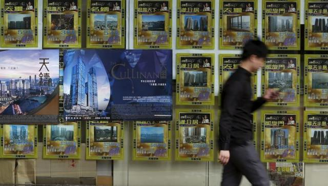 香港で売り出されている高級マンションの広告の前を通り過ぎる男性=2016年7月、ロイター