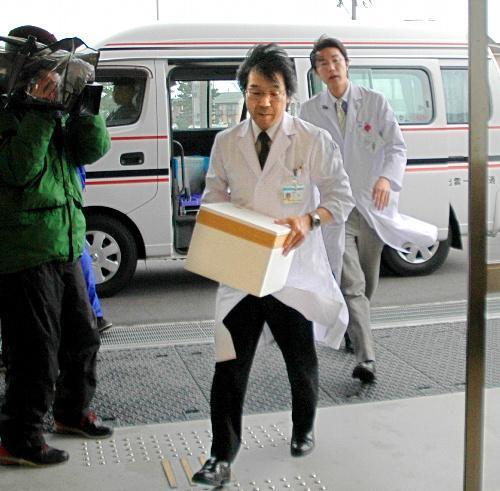 提供臓器を収めた容器を手に、病院内に向かう医師たち=2012年1月24日、出雲市塩冶町