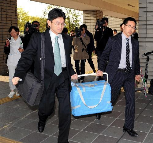 摘出された心臓が入ったクーラーボックスを運び入れる医師=2011年4月13日、大阪府吹田市