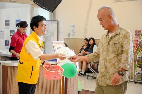 臓器提供意思表示カードとパンフレットを受け取る買い物客=宮崎市新別府町
