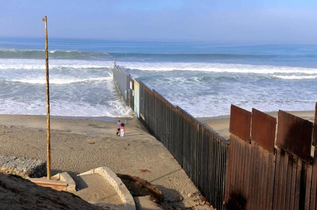 メキシコのティフアナで、海の中まで伸びた米国との国境の柵。左側がメキシコ=2016年11月5日、田村剛撮影