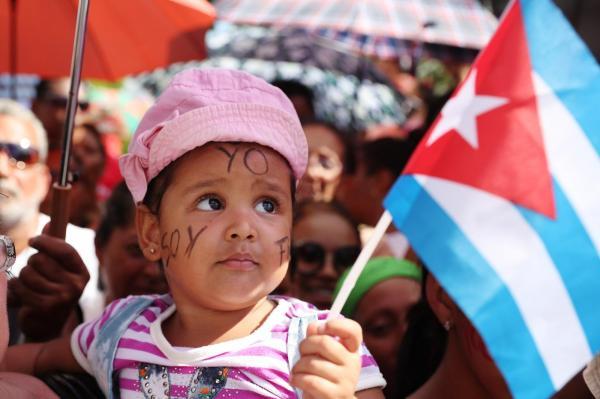 沿道で旗を振る子ども=2016年12月3日、サンティアゴデクーバ