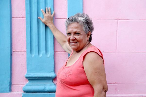 色鮮やかに塗られた民宿の壁を前にポーズをとる女性オーナー=2016年12月4日