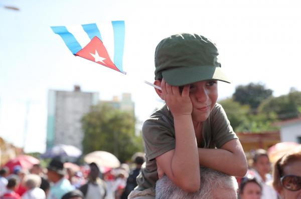 フィデル・カストロ前議長の遺灰を乗せた車列が通り過ぎた後、悲しそうな表情を見せる少年=2016年12月3日、キューバ・サンティアゴデクーバ