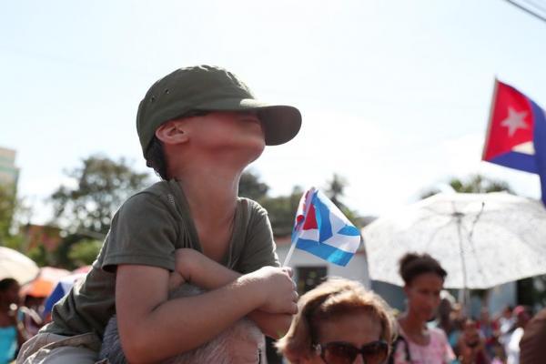 遺灰を乗せた車列が通り過ぎた後、涙を隠すように帽子を深くかぶる少年=2016年12月3日、サンティアゴデクーバ