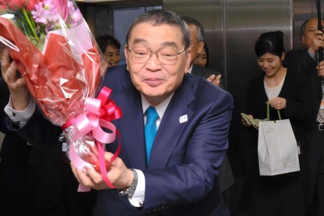 花束を手に見送りの職員らに頭を下げるNHKの籾井勝人会長