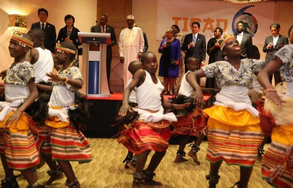 日本政府主催レセプションであしなが育英会がウガンダで支援している孤児らがダンスを披露した。壇上左端は安倍晋三首相=2016年、ケニア・ナイロビ市内のホテル