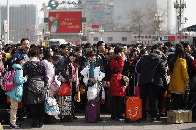 春節期間中、北京駅の前に列をつくって待つ人々=2015年2月