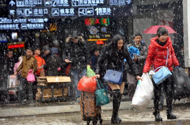 雪のなか、駅から出て家を目指す旅人