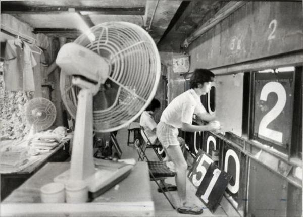1980年8月、風通しの悪いスコアボード内で、選手名や得点のボードを交換する係員