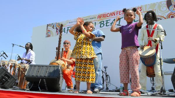 「アフリカン・フェスタ2013」のイベントで、子どもたちもステージに上がり、一緒に音楽を楽しんだ=2013年、横浜市中区