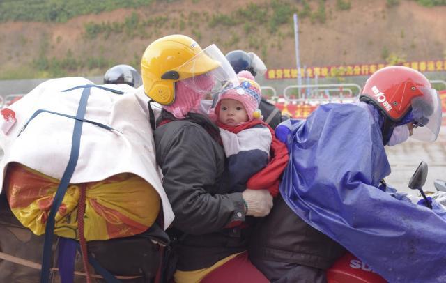 赤ちゃんを抱っこしてバイクで帰郷する出稼ぎ労働者の家族=広東、2016年2月