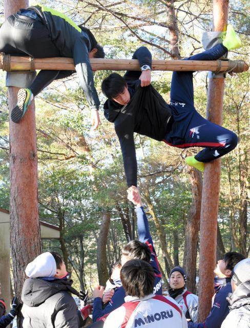 頭上3㍍近い地点に架けられた丸太を越える課題に挑む岡山の選手たち。GK櫛引(右上)が片手で人を上げようと試みる