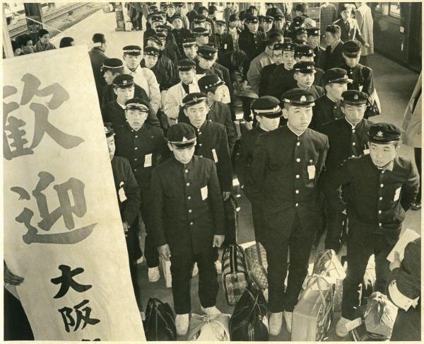 大阪にやってきた集団就職の一団。のぼりで歓迎
