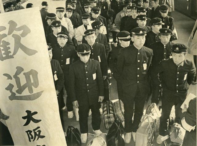 大阪駅に着いた集団就職の中学生の一団。「歓迎」ののぼりで出迎えられた(1963年)