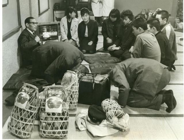 東京・上野にやってきた集団就職の一団。「どうぞよろしく」挨拶する先生(手前右)と、緊張した面持ちの若者たち(1965年)