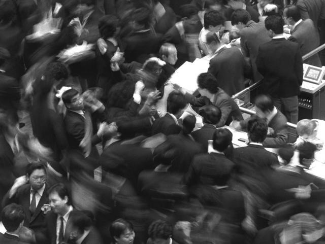1986年末の東京証券取引所。写真説明には「この年の株式市場は、膨大なカネ余りと低金利を背景に活況となり、東証平均株価は、ピークの8月20日には1万8936円24銭を記録した」とある。