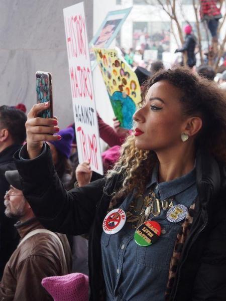 パレード中に自撮りする女性
