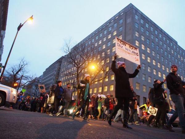 メッセージを掲げて行進する女性