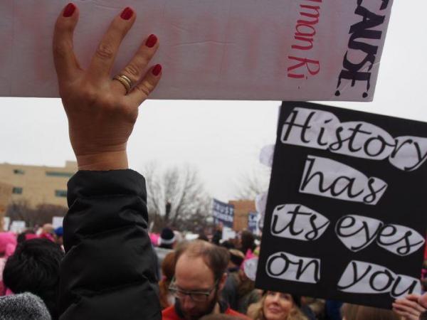 プラカードを掲げる赤マニキュアの女性