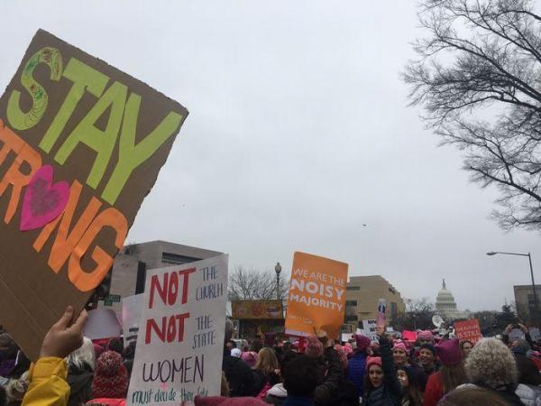 ホワイトハウスに向けて抗議のメッセージを掲げる人々