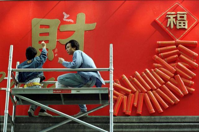 金運を表す「財」の字と爆竹を飾る若者たち=1997年1月31日、香港