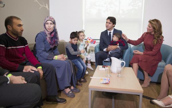 シリア難民の家族を出迎えるトルドー首相夫妻=2016年9月