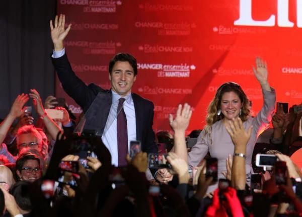 総選挙の勝利演説のステージからソフィー夫人と並んで手を振る自由党のトルドー党首=2015年10月