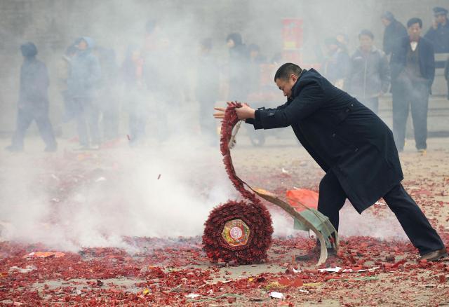 新年の幸運を祈るため、巨大爆竹を鳴らす男子=2009年1月26日、安徽省
