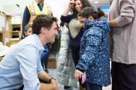 シリア難民とみられる少女と話すカナダのトルドー首相(左)