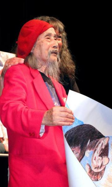 東京であった試写会の壇上で自作の猫の絵を見せるジミー・ツトム・ミリキタニさん=2007年8月14日
