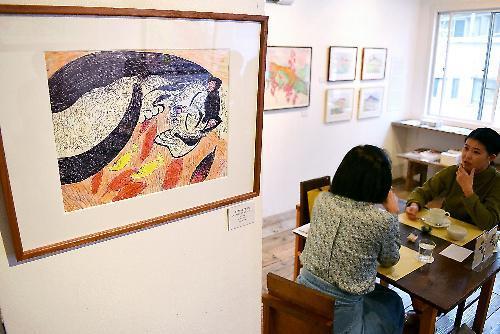 ジミー・ミリキタニさんが描いたが飾られたカフェ