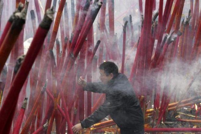 新年を祝うため、爆竹の煙の中で巨大線香を焚く市民=2009年1月26日、四川省雅安市