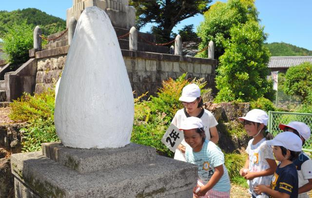 校庭の「歯の塔」に自分の乳歯を納める小学生ら=岐阜市