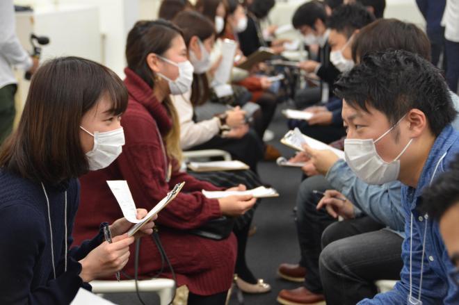 マスクを着けたまま、2人1組になって話す参加者=東京都千代田区