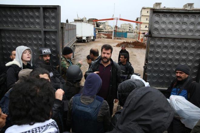 2015年1月、トルコ南部の町の国境ゲートに報道陣が集まる。トルコ側の担当者がシリア入国の手順を説明する。中央奥に見えるのがシリア北部アインアルアラブ(コバニ)の町並みだ