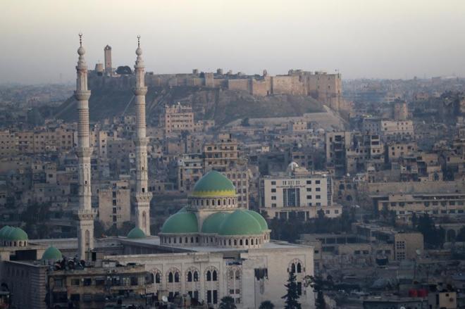 ホテルの窓から見える、夕日に照らされるアレッポ城(奥)。周辺は「古代都市アレッポ」としてユネスコの世界遺産に登録されています。手前はドームが美しいモスクです。