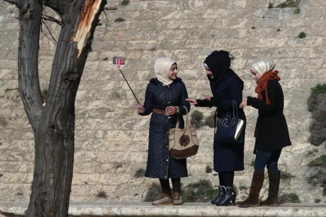 世界遺産「アレッポ城」の前で自撮りするシリアの女性たち