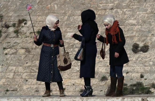 アレッポ城のお堀の塀に立って自撮り棒でセルフィーを撮る女性たち。戦闘が続いていた旧市街にも、ようやく訪れることができるようになりました